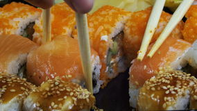 Sticks Take Sushi from Sushi Box. Variety of types sushi with red caviar, fish, Philadelphia cheese and chopsticks close-up. Set of delicious Japanese sushi stock video