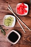 Sticks, Wasabi, soy sauce and pickled ginger for sushi on brown wooden table background. Top view Stock Image