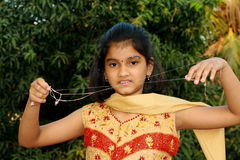 This is a sticky bubblegum thread. A small Indian girl stretching a bubble gum thread Royalty Free Stock Photography