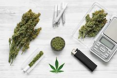 Joint and a grinder with crushed weed Leaf of cannabis, buds of marijuana, unrolled weed on a white wooden background top view. Sticky buds of marijuana flowers stock photo
