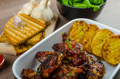 Sticky chicken wings with garlic panini bread Stock Images
