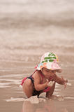 Sticky Fingers. Little girl discovering sand at the beach Stock Photos