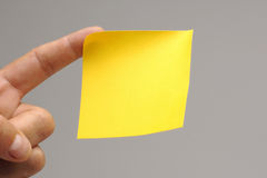 Sticky note. Yellow sticky note at finger tips royalty free stock images