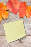 Sticky note on the board with autumnal leaves Royalty Free Stock Photo
