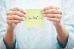 Sticky note with Contact us text. Yoga instructor holding sticky note with Contact us text Stock Photography
