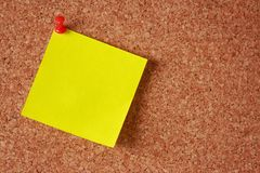 Sticky note on a cork board. Yellow sticky note with a red pin on a cork board Stock Photo