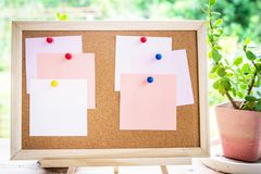 Sticky note on cork board with little tree,garden background stock image