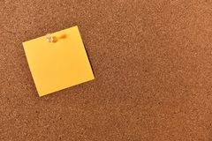 Sticky Note and Corkboard. An image of a bright sticky note pinned to a wooden cork-board royalty free stock photos