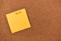 Sticky Note and Corkboard. An image of a bright sticky note pinned to a wooden cork-board stock photography