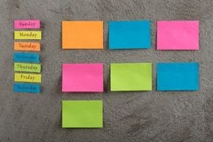 Sticky note with days of week on grey cement background. Monday, Tuesday, Wednesday, Thursday, Friday, Saturday, and Sunday. Empty. Many colorful sticky note royalty free stock photography
