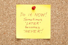 Sticky Note Do it Now. Do it Now, written on an yellow sticky note on a cork bulletin board royalty free stock image