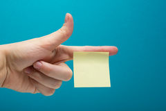 Sticky note, finger up of thumb, yellow reminder on blue background. Royalty Free Stock Photos