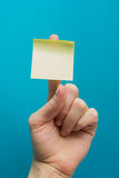 Sticky note, finger up of thumb, yellow reminder on blue background. Hand holding yellow note reminder on finger with copy space for ad on blue background royalty free stock photography