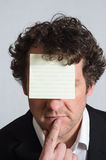 Sticky Note on Forehead. A curly haired man in a suit with shirt slightly open and no tie, resting finger on chin in a contemplative manner, with a blank, lined Stock Photos