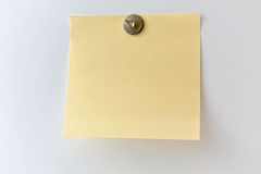 Sticky note on a grey wall. Yellow sticky note and metallic tack on a grey wall Royalty Free Stock Photos