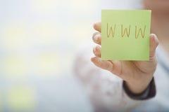 Sticky note with internet address. Woman holding sticky note with Internet address Royalty Free Stock Photo