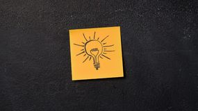 Sticky note on the blackboard. Sticky note with light bulb idea icon on the blackboard Stock Photography