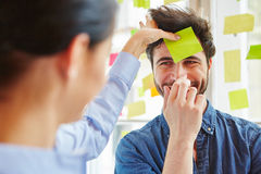 Sticky note on man's forehead. During team training game in workshop Stock Photos
