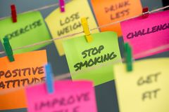 Sticky note with message stop smoking hanging on rope royalty free stock images