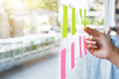 Sticky note paper reminder schedule board on glass windows. Sticky note paper reminder schedule board. Business people meeting and use post it notes to share royalty free stock photos