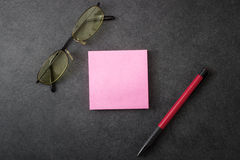 Sticky note, pen and  glasses Stock Photos