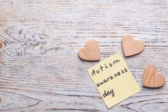 Sticky note with phrase. `Autism awareness day` on wooden background royalty free stock image