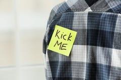 Sticky note with phrase. `Kick me` on man`s back, closeup. April fool`s day prank Stock Photography