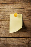 Sticky note with pin over wooden background Stock Image