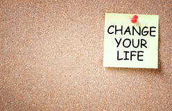 Sticky note pinned to board with the phrase change your life.  Stock Photos