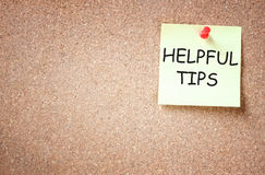 Sticky note pinned to cork board with the phrase helpful tips written on it room for text.  stock image