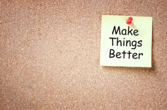 Sticky note pinned to cork board with the phrase make things better written on it room for text.  royalty free stock photos