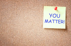 Sticky note pinned to cork board with the phrase you matter. Sticky note pinned to cork board with the phrase you matter pic Royalty Free Stock Photography