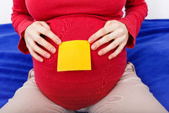 Sticky note on pregnant woman belly Royalty Free Stock Photos