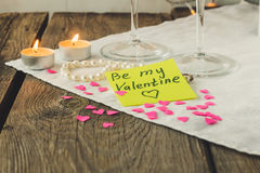 Sticky note for Saint Valentine's day and tea lights on wooden t Stock Photography