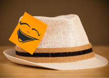 Sticky note with smiley face sticked on hat Stock Photo