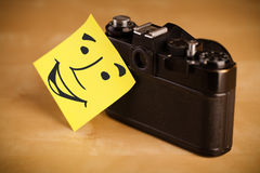 Sticky  note with smiley face sticked on a photo camera Stock Image