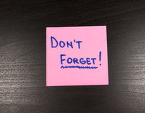 Sticky note with text Don't forget on it,  on wooden background.  Royalty Free Stock Photo