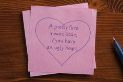 Sticky note with text A face means little,if you have an ugly hea Royalty Free Stock Photography