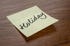 Sticky note with the text Holiday stock photo