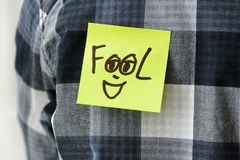 Sticky note with word. `Fool` on man`s back, closeup. 1st April prank royalty free stock photos