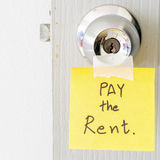 Sticky note write a message pay the rent Royalty Free Stock Image