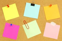 Sticky notes on bulletin board. Sticky notes of various colors and fasteners on a bulletin board Stock Images