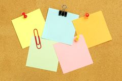 Sticky notes on bulletin board. Sticky notes of various colors and fasteners clustered on a bulletin board Royalty Free Stock Image