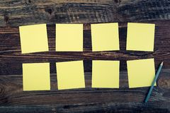 Sticky notes. Bunch of yellow sticky notes on the wooden background royalty free stock photos