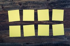Sticky notes. Bunch of yellow sticky notes on the wooden background royalty free stock image