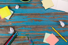Sticky notes, color pencils, paper pins and paper balls. On wooden plank Royalty Free Stock Images