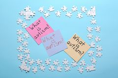 Sticky notes with phrase. `What is autism?` and puzzle pieces on color background Royalty Free Stock Images