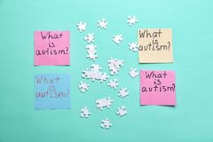 Sticky notes with phrase. `What is autism?` and puzzle pieces on color background, flat lay Royalty Free Stock Photography