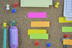 Sticky notes, pin, key and tag name on cork board Stock Photos