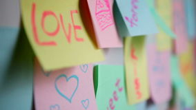 Sticky paper adhesive note on wall, with marriage or relationship, love concept. Colored adhesive note on the wall stock video footage